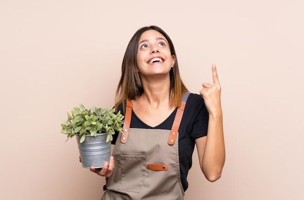 指を持ち上げながら解決策を実現しようとしている植物を保持している若い女性