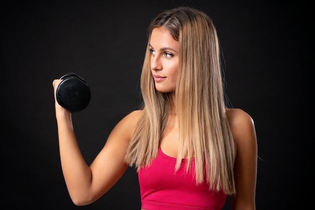 孤立した黒い壁を越えて重量挙げを作る若いスポーツブロンドの女性