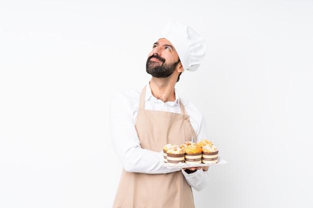 Молодой человек, держащий торт сдобы на изолированной белой стене, смотрящей, улыбаясь