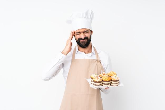 頭痛で孤立した白い壁にマフィンケーキを置く若い男