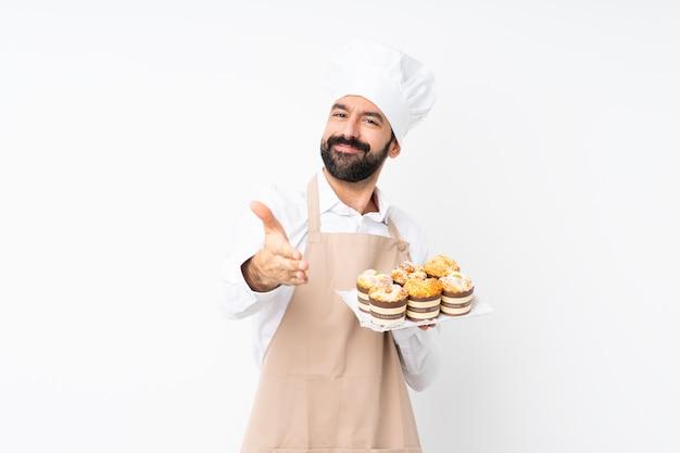 かなりの閉鎖のために手を振って孤立した白い壁にマフィンケーキを置く若い男