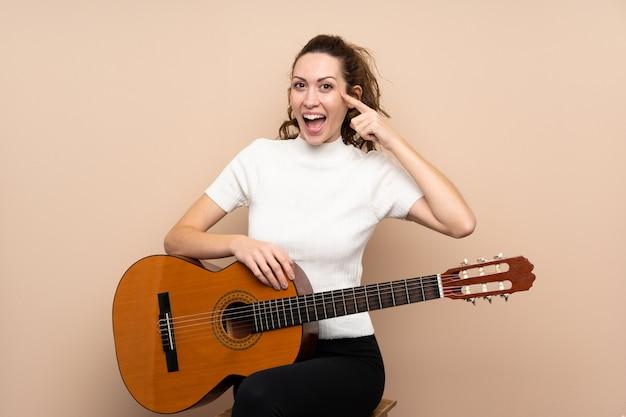 解決策を実現しようとしている孤立した壁の上のギターを持つ若い女性