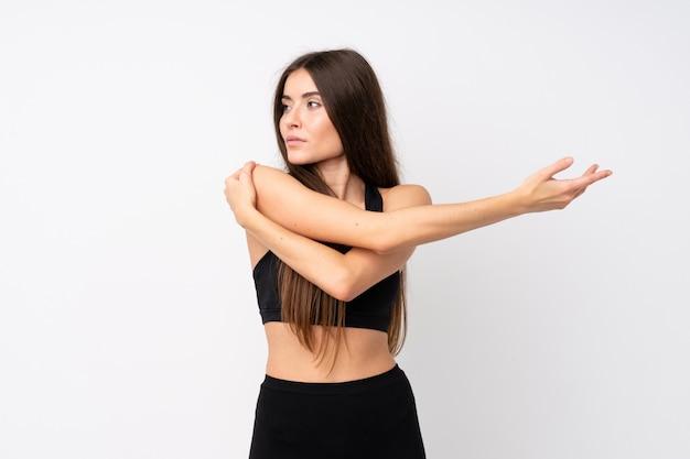 腕を伸ばして分離の白い壁の上の若いスポーツ女性