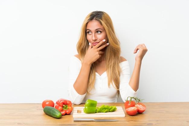 Молодая белокурая женщина с овощами в таблице думая идея