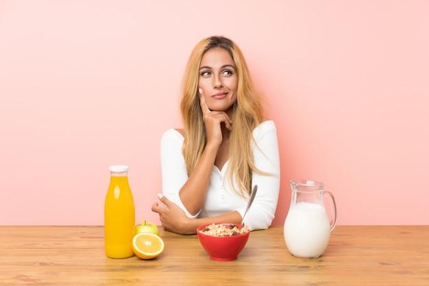 Молодая белокурая женщина имея молоко завтрака думая идея