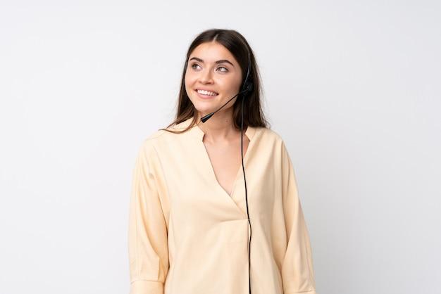 Молодая женщина телемаркетера над изолированной белой стеной смеясь над и смотря вверх