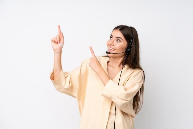 人差し指で素晴らしいアイデアを指している孤立した白い壁の上の若いテレマーケティング女性