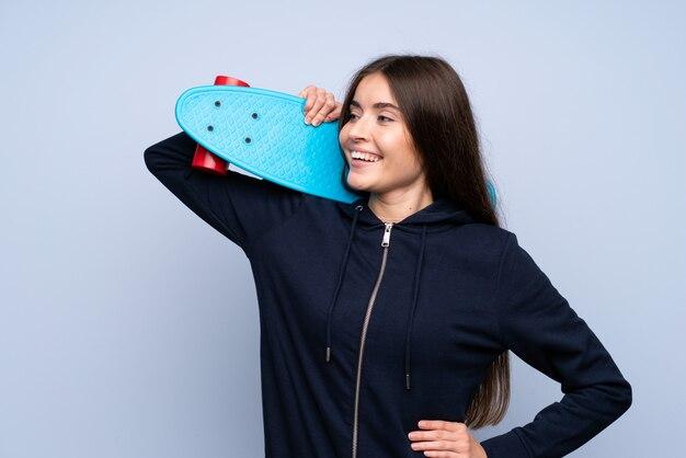 スケートと見ている側で孤立した青い壁の上の若い女性