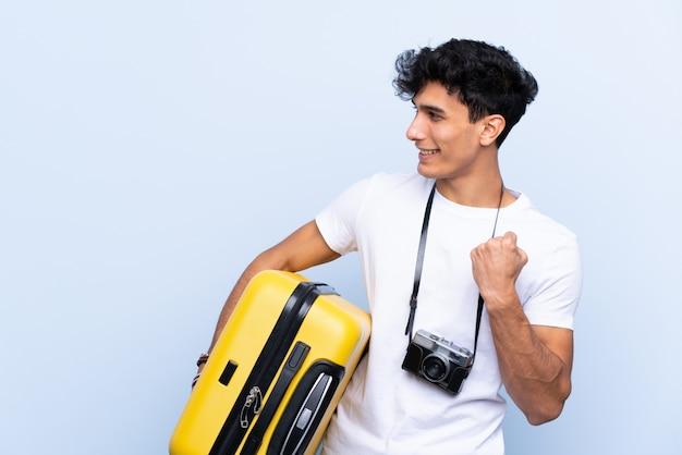 Молодой аргентинский путешественник человек над синей стеной празднует победу