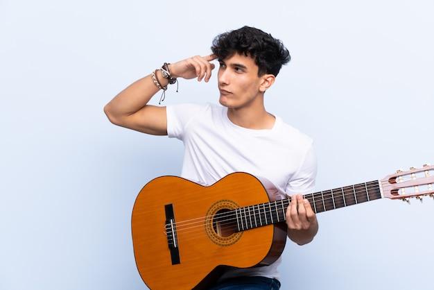 疑問を持つ分離された青い壁の上のギターと混乱の表情を持つ若いアルゼンチン人男性