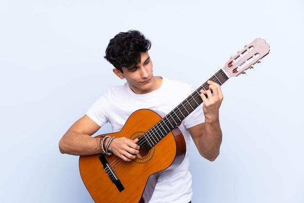孤立した青い壁の上のギターを持つ若いアルゼンチン人