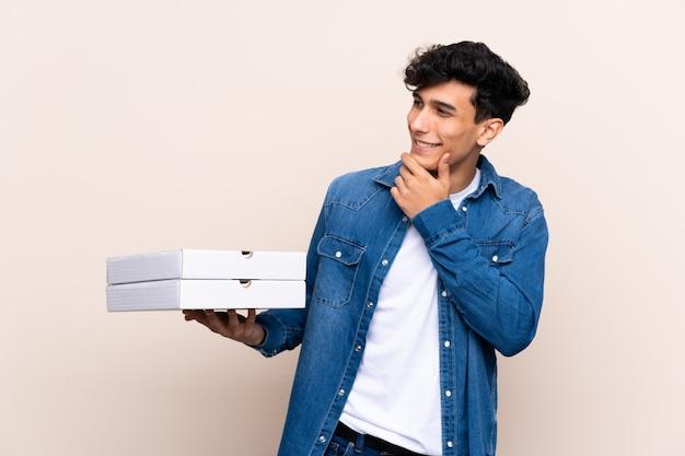 Молодой аргентинский человек, держащий пиццу над изолированной стеной, думает идея и смотрит в сторону
