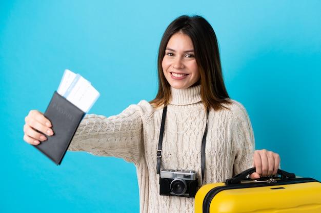 孤立した青い壁にスーツケースとパスポートを保持している旅行者の女性