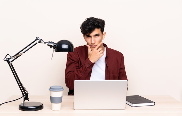 Молодой аргентинский мужчина в таблице с ноутбуком на своем рабочем месте, думая, идея