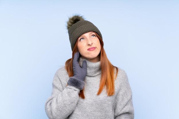 Рыжая молодая русская женщина в зимней шапке над синей стеной думает идея