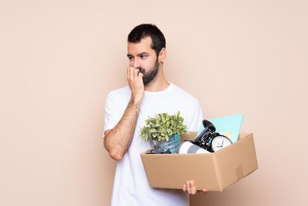 箱を持って、疑いを持つ孤立した壁を越えて新しい家に移動する男
