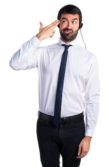 Молодой человек с гарнитурой, делая самоубийственный жест