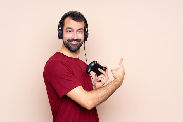 Человек играет с контроллером видеоигры над изолированной стеной, указывая назад