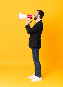 Полнометражный бизнесмен над изолированной желтой стеной крича через мегафон