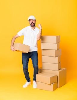 Полная длина доставщик среди коробок над изолированной желтой стеной празднует победу в позиции победителя