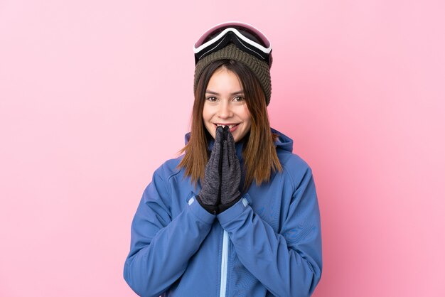 ピンクの壁の上のスキーグラスを持つ若い女性