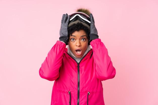 孤立したピンクの壁を越えてスキーグラスを持つアフリカ系アメリカ人の女性