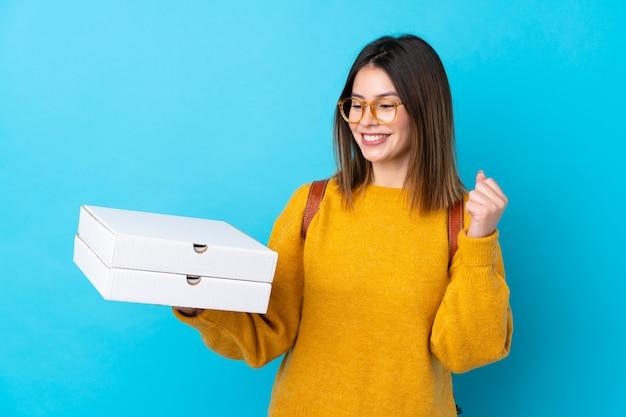 Молодая женщина держит коробки для пиццы над синей стеной