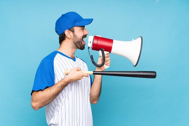 メガホンを通して叫んで孤立した青の上に野球をしている若い男