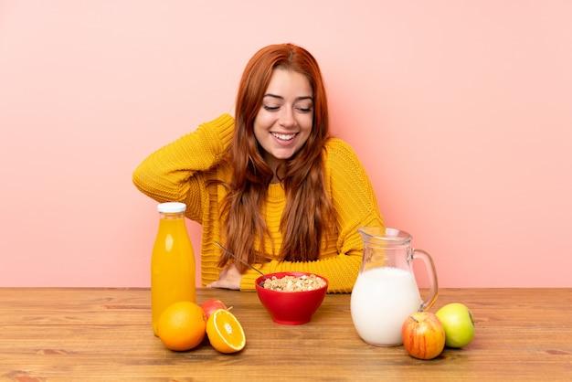 Рыжая девушка подросток завтракает в таблице смеется