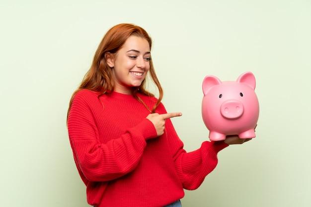 Рыжая девушка-подросток со свитером на зеленом фоне держит большую копилку