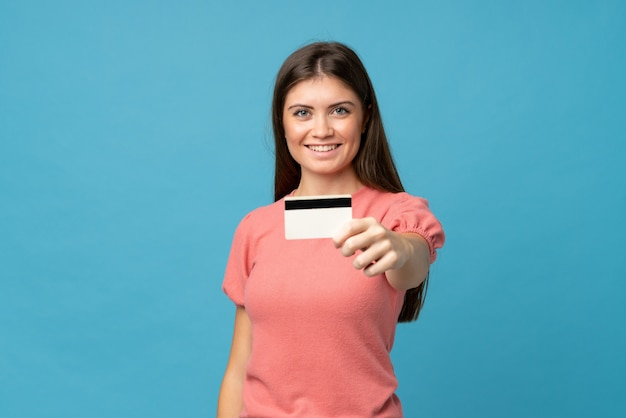 クレジットカードを保持している分離された青の上の若い女性