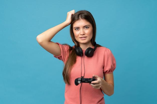 Молодая женщина над изолированным голубым играя на видеоиграх