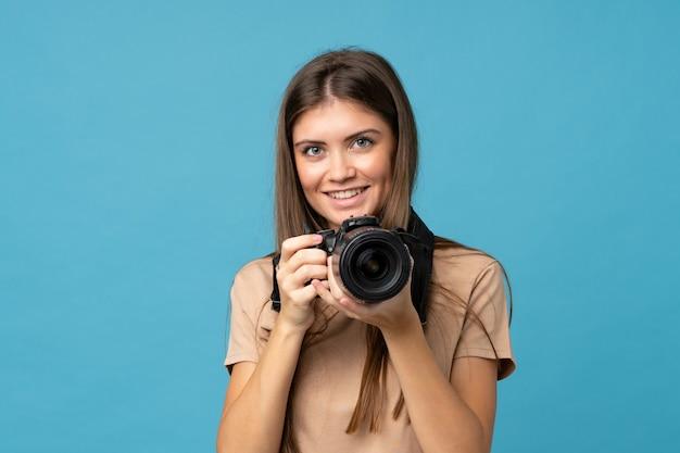 プロのカメラで分離された青の上の若い女性