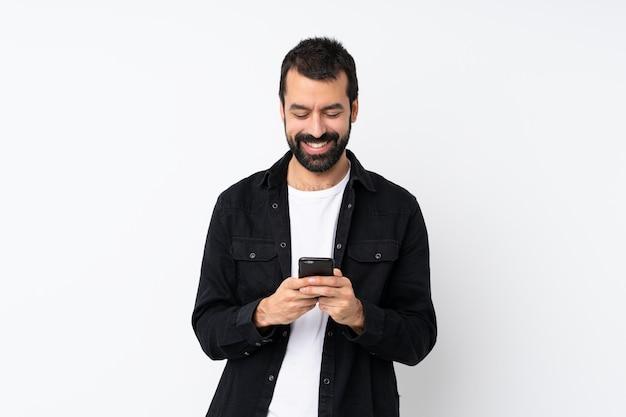 Молодой человек с бородой на белом фоне, отправив сообщение с мобильного телефона