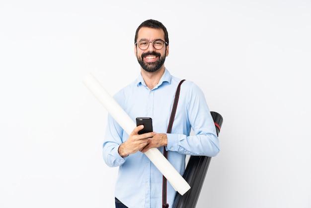 Молодой архитектор человек с бородой на белом фоне, отправив сообщение с мобильного телефона