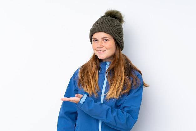 来て招待する側に手を伸ばす分離白の上の冬の帽子とウクライナのティーンエイジャーの女の子