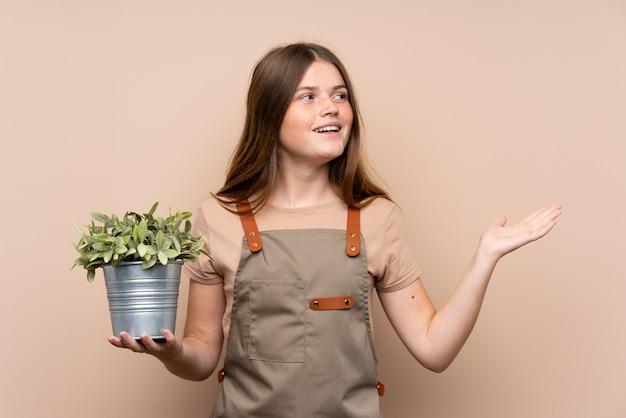 Украинский подросток садовник девочка держит растение с удивленным выражением лица