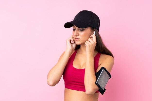 Молодая девушка спорта над изолированной розовой слушая музыкой