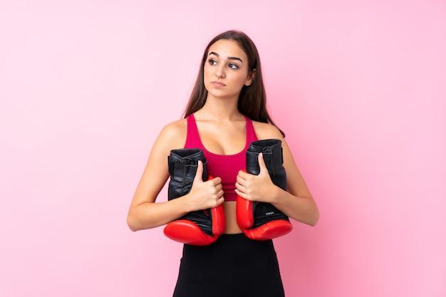 ボクシンググローブと分離されたピンクの上の若いスポーツ少女