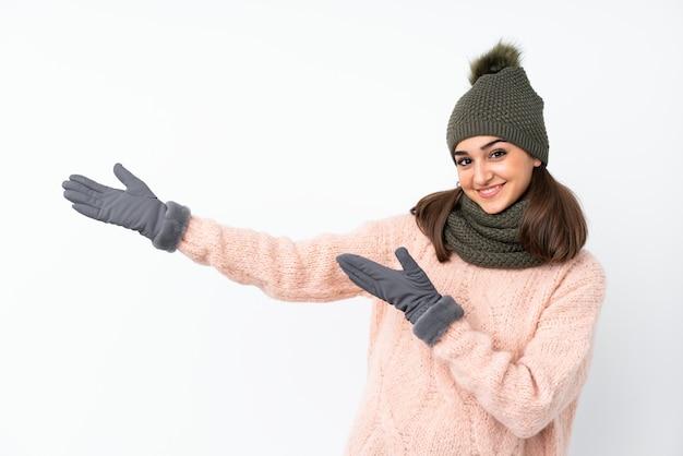 来て招待する側に手を拡張する分離白で冬の帽子を持つ少女