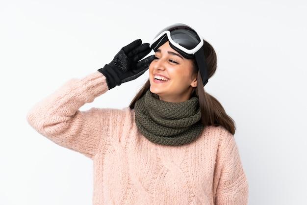 Девушка-лыжница в сноуборд-очках над изолированной белой стеной что-то поняла и намеревается найти решение