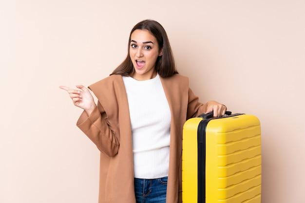 Путешественник женщина с чемоданом удивлен и указывая пальцем в сторону