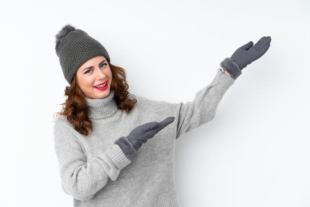 来て招待する側に手を伸ばす分離白で冬の帽子を持つ若いロシア人女性