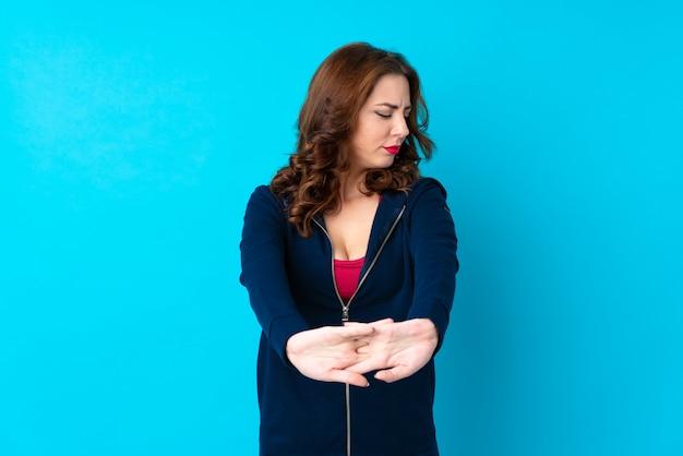 孤立した青いストレッチアーム上の若いスポーツ女性
