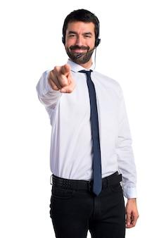 フロントを指しているヘッドセットを持つ若い男