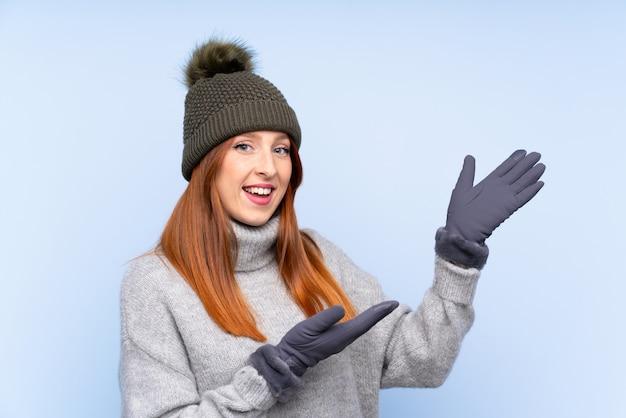 来て招待する側に手を伸ばす分離された青い上の冬の帽子を持つ若い赤毛ロシア女性