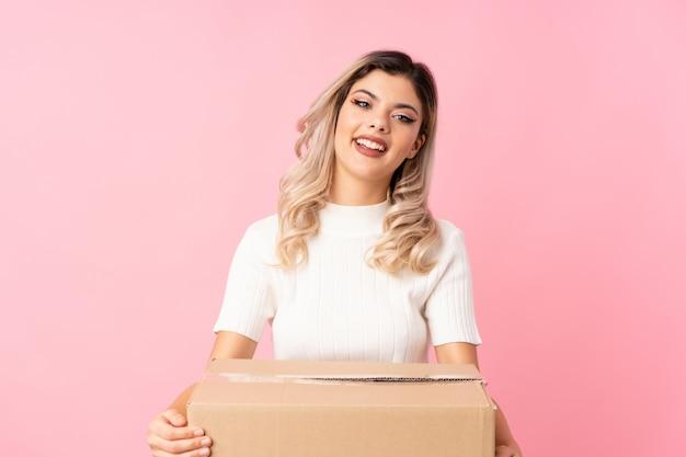 別のサイトに移動するボックスを保持している分離されたピンクの上のティーンエイジャーの女の子