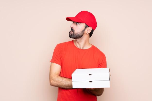 混乱して表情で分離された上にピザをかざす若い男