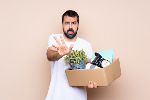 箱を持って、孤立した緊張のストレッチ手の上に新しい家に移動する男
