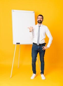 製品を提示する側を指している孤立した黄色の上にホワイトボードでプレゼンテーションを行う実業家の全身ショット